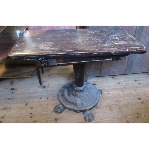 5 - A 19th century rosewood fold over games table, with carved decoration, and raised on a column to a c...
