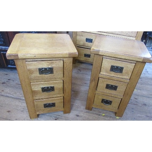 7 - A pair of modern oak bedside cabinets, fitted with three drawers, 16ins x 18is x height 27.5ins