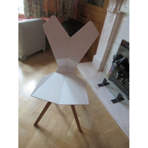 12 - A white plastic chair with geometric shaped back and seat raised on metal chairs