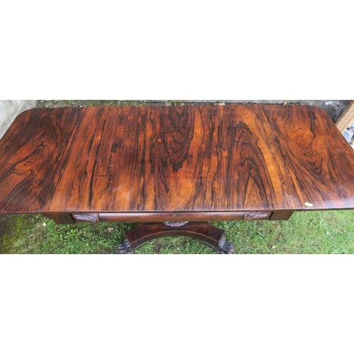 30 - A 19th century rosewood sofa table raised on a platform base