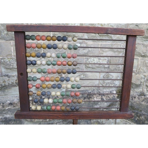 35 - An Antique abacus, with coloured wooden beads, on a turned column, with metal base, height 58ins