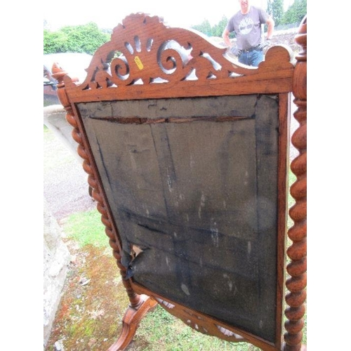 42 - A walnut fire screen, the embroidered panel flanked by barley twist columns, below a carved frieze, ...