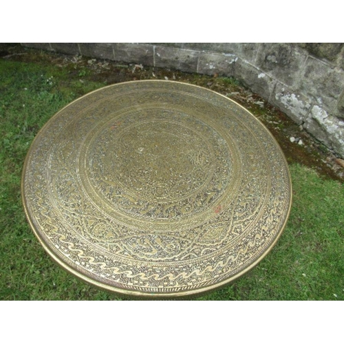45 - A brass Benares topped table, the wooden folding base with carved and inlaid decoration, diameter 23...