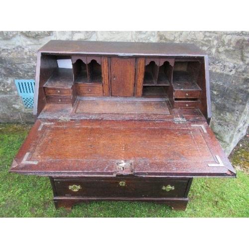 48 - A late Georgian oak bureau, the fall flap opening to reveal cupboards, secret drawers, pigeonholes a...