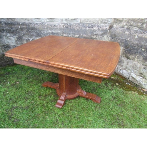 51 - An oak extending dining table, raised on a central cylindrical column, in the Art Deco style, having...
