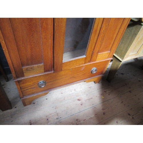 41 - An Arts and Crafts style wardrobe, the mirror door flanked by two panels with stained glass inserts,...