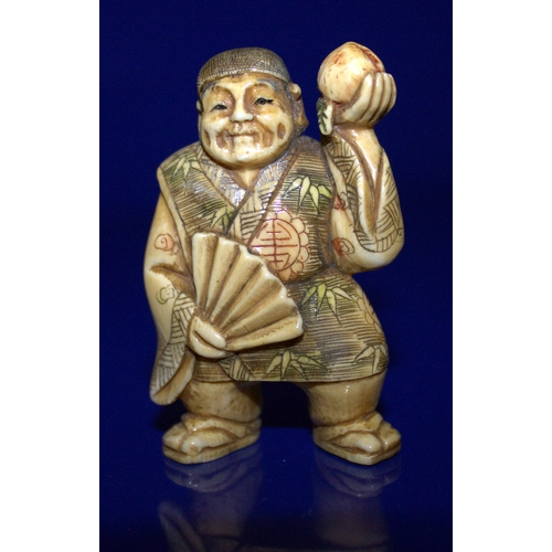 307 - A Meiji Period Stained Ivory Netsuke Of A Man Holding A Peach, Signed To Base With Red Signature...