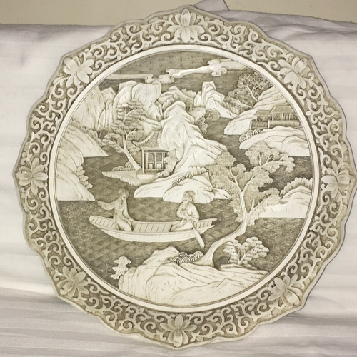 245 - A nicely made, white cinnabar decorative plate with scroll and flower rim and a couple in a boat to ...