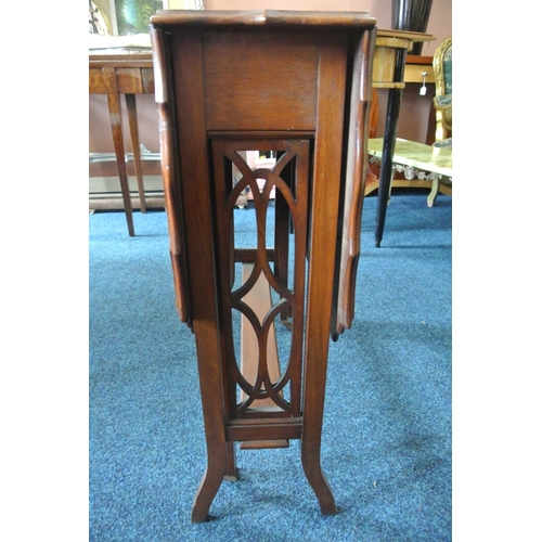24 - An antique mahogany drop leaf table with decorative legs....