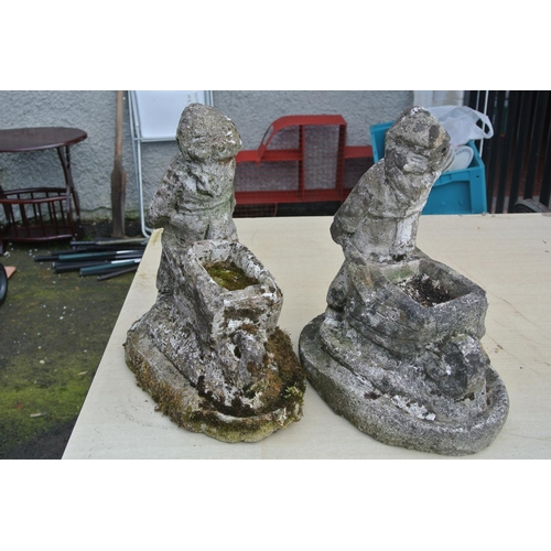 1b - A pair of concrete planters in the form of men pushing wheelbarrows....