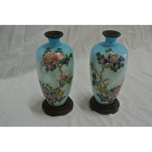 48 - A pair of miniature enamel vases and stands...
