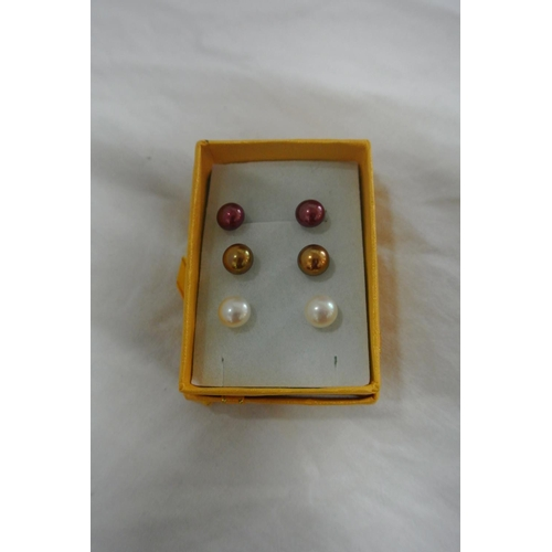 52 - A boxed set of three multicoloured pearl earrings...