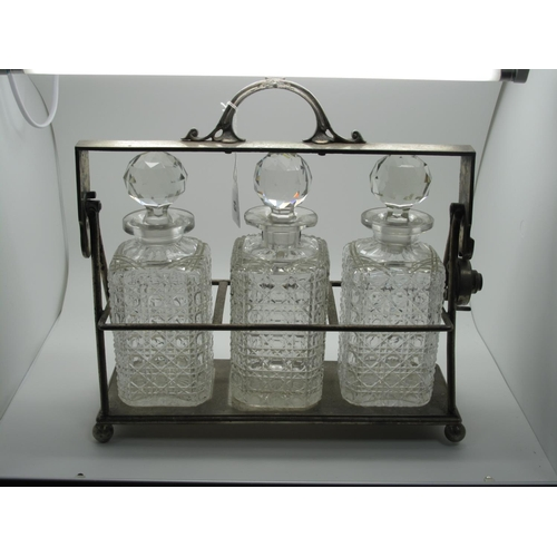 13 - A JD&S Electroplated Three Bottle Locking Tantalus, of plain design, with three hobnail cut glass st...