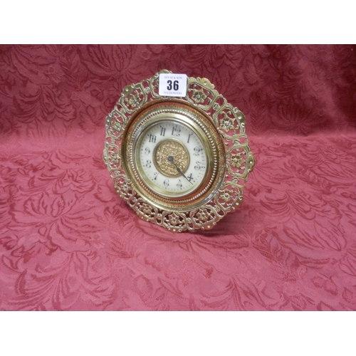 36 - A Victorian mantel clock, cream enamel chapter ring, in a brass case with pierced floral border, str...