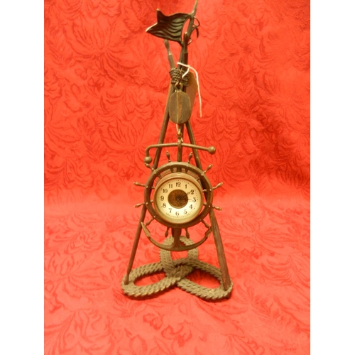 43 - A Victorian clock with cream enamel dial, in a metal case in the form of a ships wheel, anchor and b...