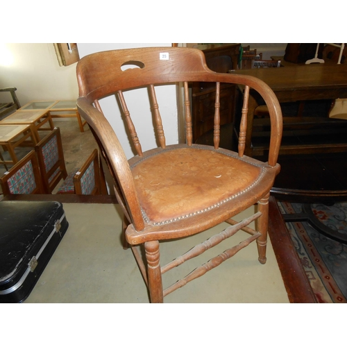25 - An elm framed desk chair with curved spindle back, hard seat, on turned legs...