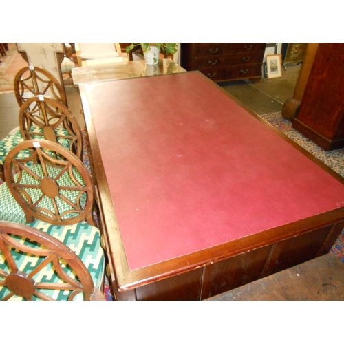 27 - A mahogany desk with red rexine writing surface, fitted drawers to each pedestal - 72in. x 42in....