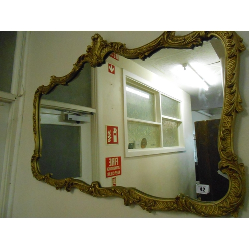 42 - A rectangular shaped wall mirror in a gilt scroll frame - 27in. x 40in....