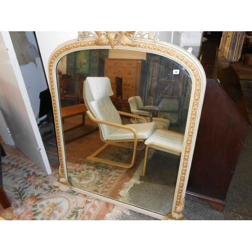 48 - A Victorian overmantel mirror in a cream and gold painted frame, the top surmounted by flowers and f...