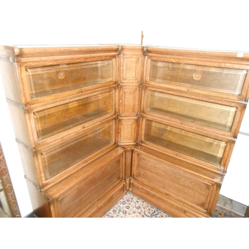 59 - An oak Globe Wernicke four section corner bookcase with bevelled glass up and over doors...