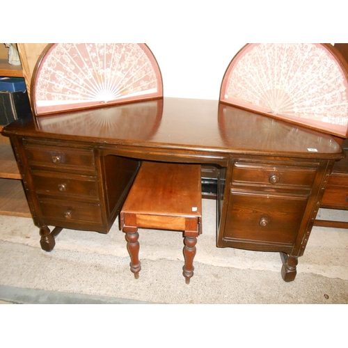 60 - An Ercol dark oak desk fitted one narrow and one wide drawer to one pedestal and three drawers to th...