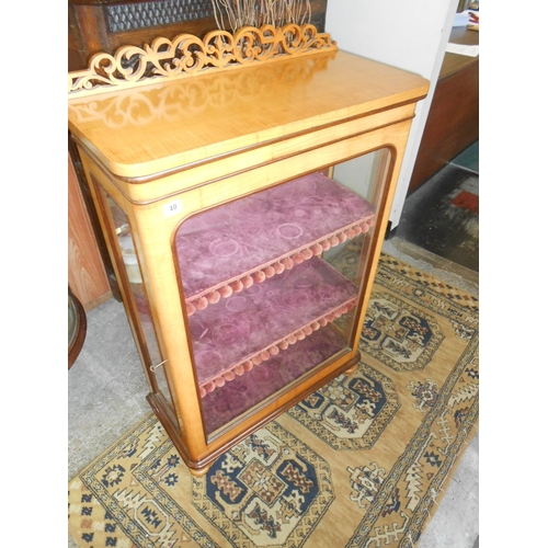 40 - A Continental Victorian satinwood pier cabinet with fret carved scrolling back, fitted glass door an...