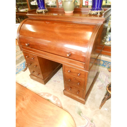 42 - A 19th Century mahogany desk, the roll top with 3/4 tray top enclosing fitted interior, fitted three...