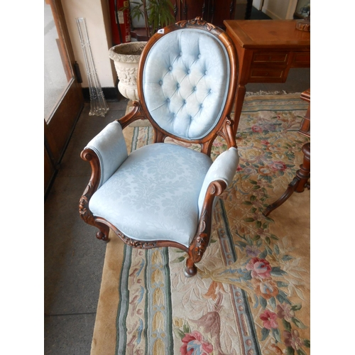 48 - A Victorian walnut framed armchair with scroll carved oval back, the seat, back and armpads upholste...