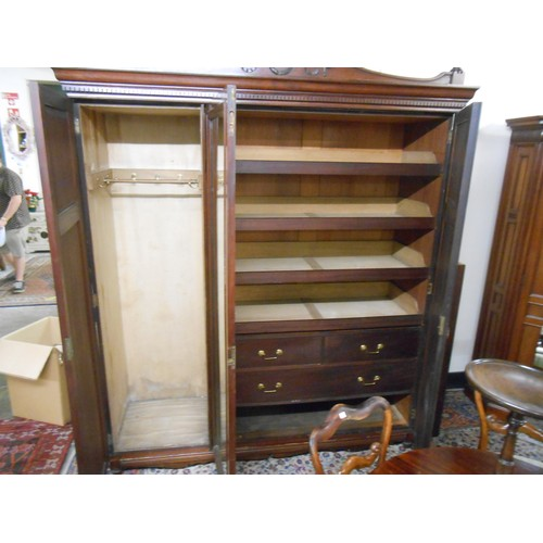 46 - An Edwardian walnut wardrobe with scroll pediment, fitted centre mirrored door flanked to each side ...