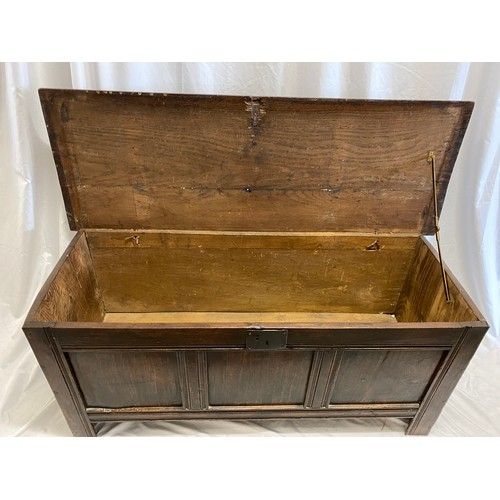 35 - An antique oak coffer with hinged lid and three panels to the front, on stile feet - 55in. wide