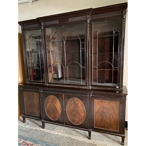 45 - An Edwardian mahogany breakfront bookcase, the upper part fitted three glass doors with arched glazi...