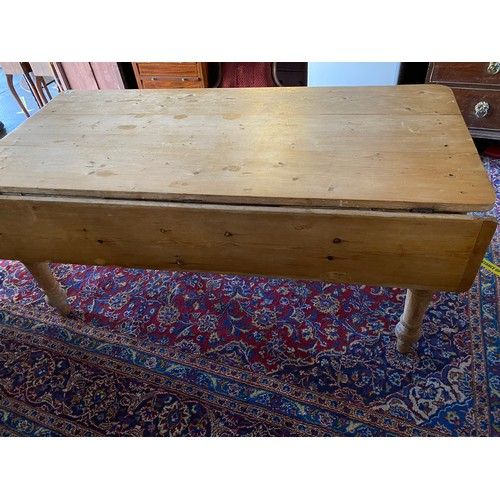 38 - A pine kitchen table with drop flap, fitted two drawers, on turned legs and pointed toes - 66in. wid...