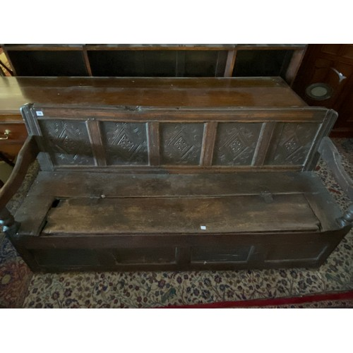 39 - An antique oak hall bench with five carved panels to the back, hinged seat, scroll arms - 70in. wide