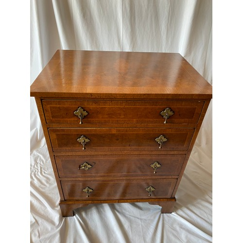 48 - A reproduction walnut and crossbanded straight front chest fitted four wide drawers, pear drop style...
