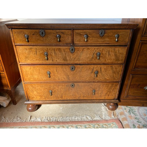 51 - A William and Mary walnut veneered straight front chest with quarter veneer to the top, fitted two n...