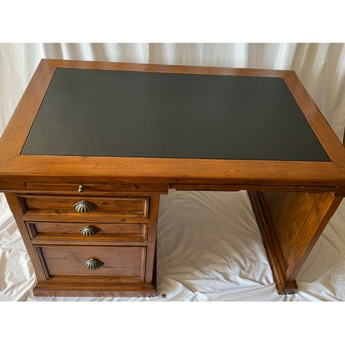 56 - A modern stained pine desk with inset writing surface, fitted two slides and folio drawer and three ...