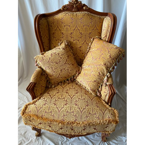 58 - A reproduction French style semi wing armchair with carved floral cresting rail, upholstered seat an...