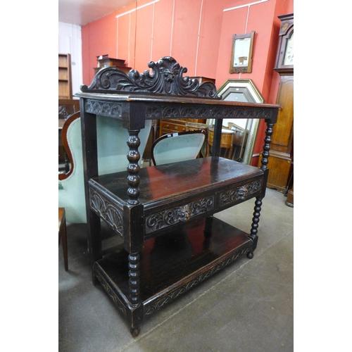 55 - A Victorian Jacobean Revival carved oak buffet...