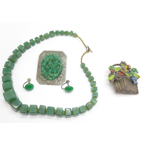 962 - A Chinese silver and enamel flower basket brooch, a jade coloured necklace and earrings, and a carve...