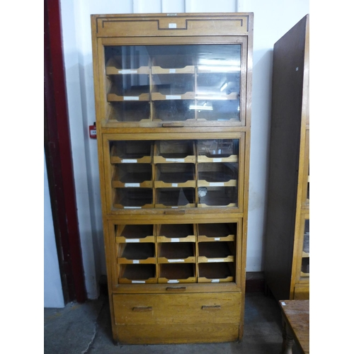 30 - A mid 20th Century oak haberdashery shop cabinet...