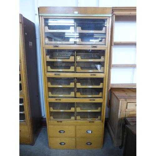 32 - A mid 20th Century oak haberdashery shop cabinet...