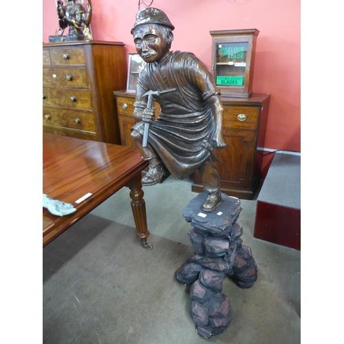 54 - A carved wood figure of a blacksmith, on pedestal base...