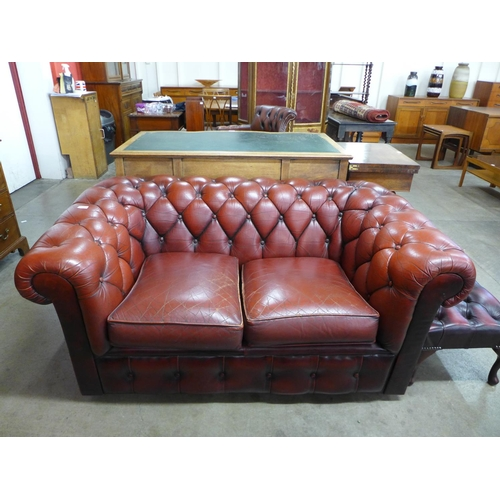 66 - A red leather Chesterfield settee...