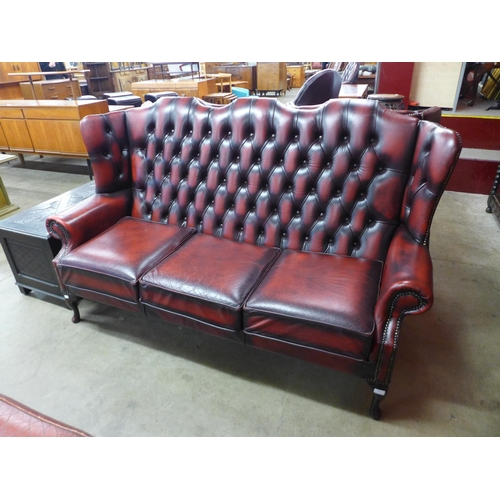 67 - A red leather Chesterfield wingback settee...
