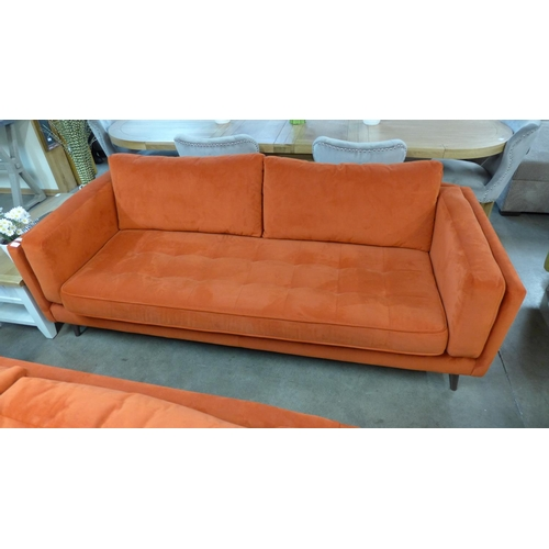 1308 - An orange velvet three seater sofa...
