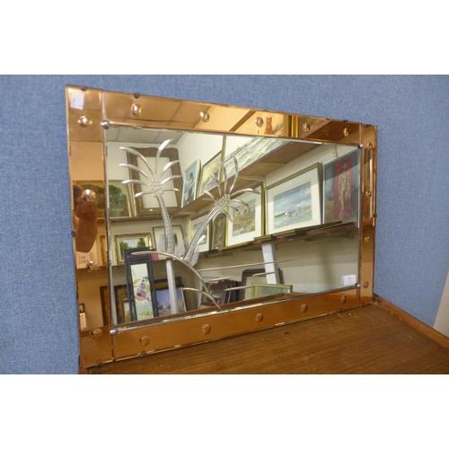 45 - A peach glass mirror...