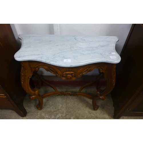 49 - A small rococo style mahogany and marble topped console table...