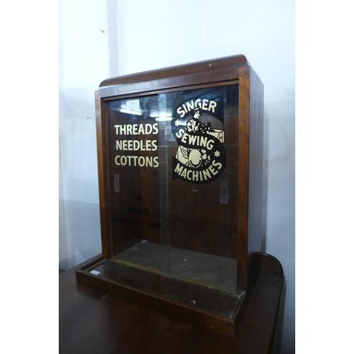 61 - A mahogany counter top shop display cabinet, bearing Singer Sewing Machines inscription to doors...