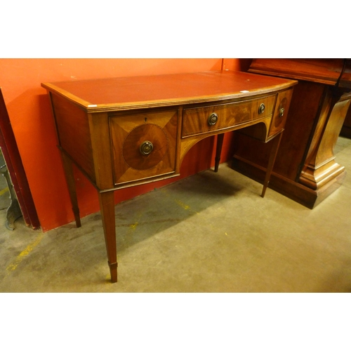64 - An Edward VII Maple & Co. inlaid mahogany bow front three drawer writing table...