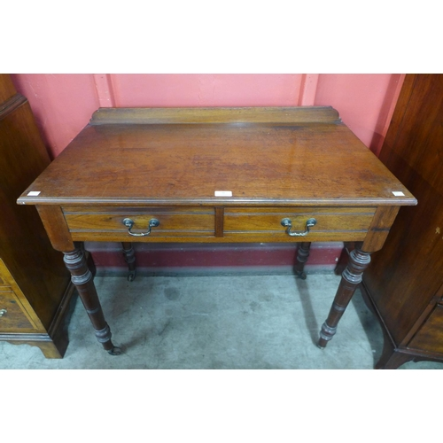 76 - A Victorian Jas. Schoolbred & Co. walnut two drawer side table...